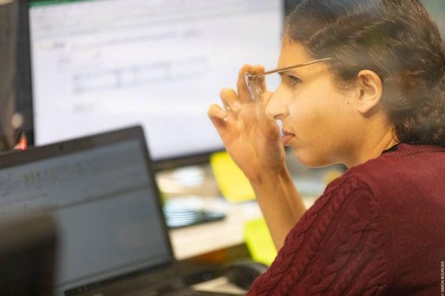 Collaboratrice GoodBuy media en gros plan, de profil, visage tourné vers son ordinateur, en train d'enlever ses lunettes