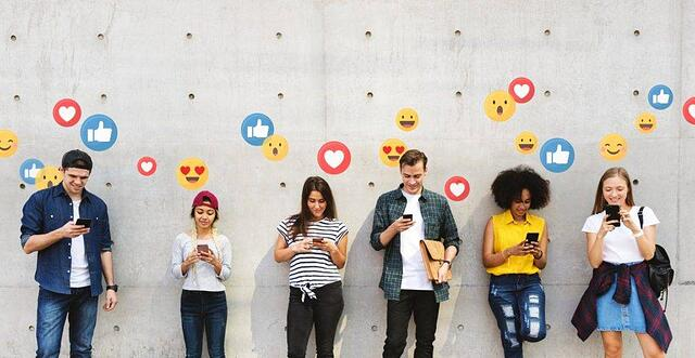 Plusieurs personnes contre un mur, bulles de réactions autour d'elles (likes, coeurs, etc.)